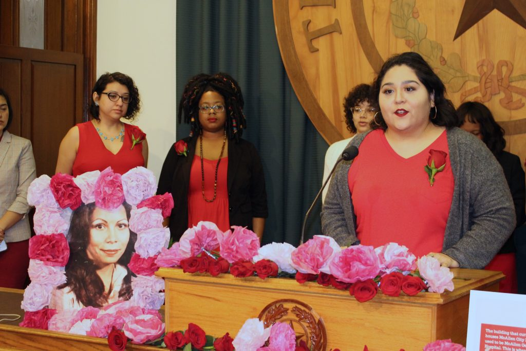 In the foreground, a framed photo of Rosie Jimenez, a young Chicana woman, is adorned with paper roses as Erika Galindo, Lilith Fund Organizer, speaks at the podium next to the photo. In the background, five women wearing red stand behind Erika in the press briefing room at the Texas Capitol.